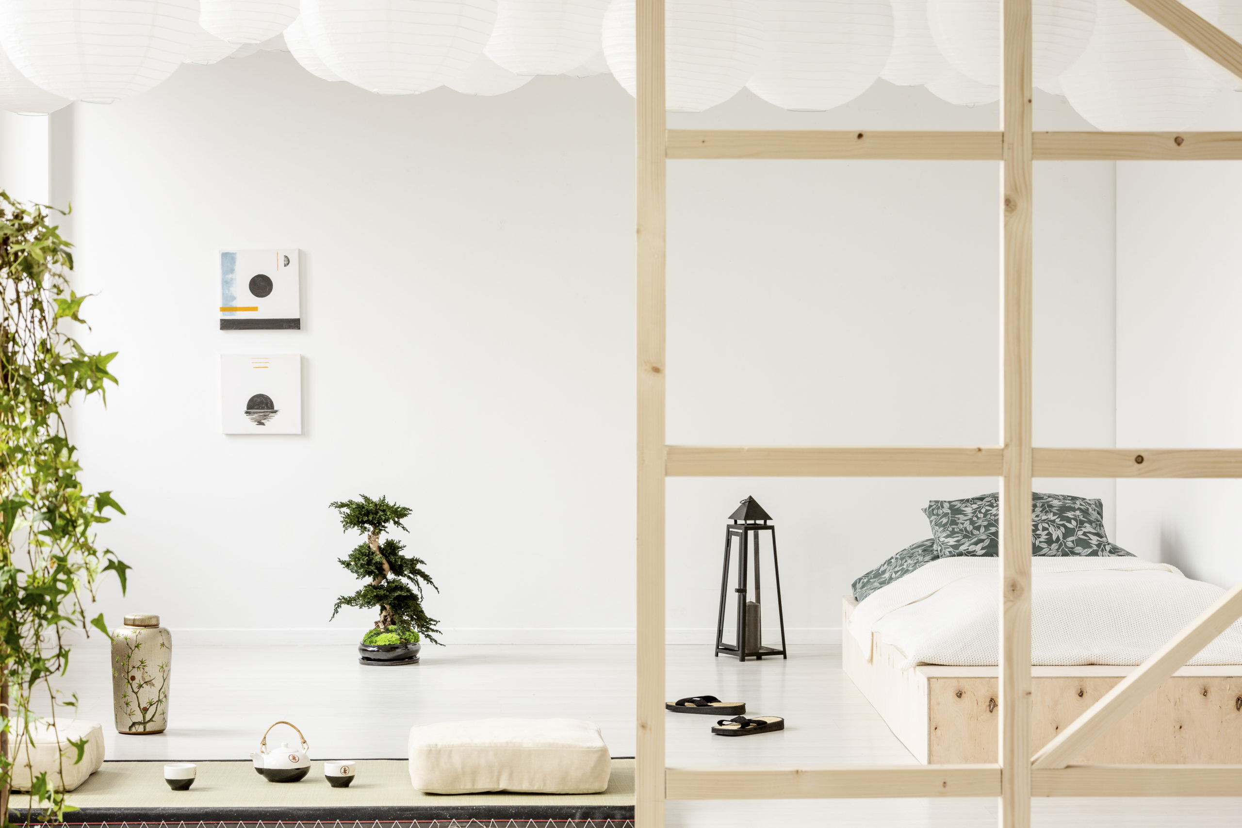 Posters on white wall above bonsai in bedroom interior with lantern next to wooden bed. Real photo