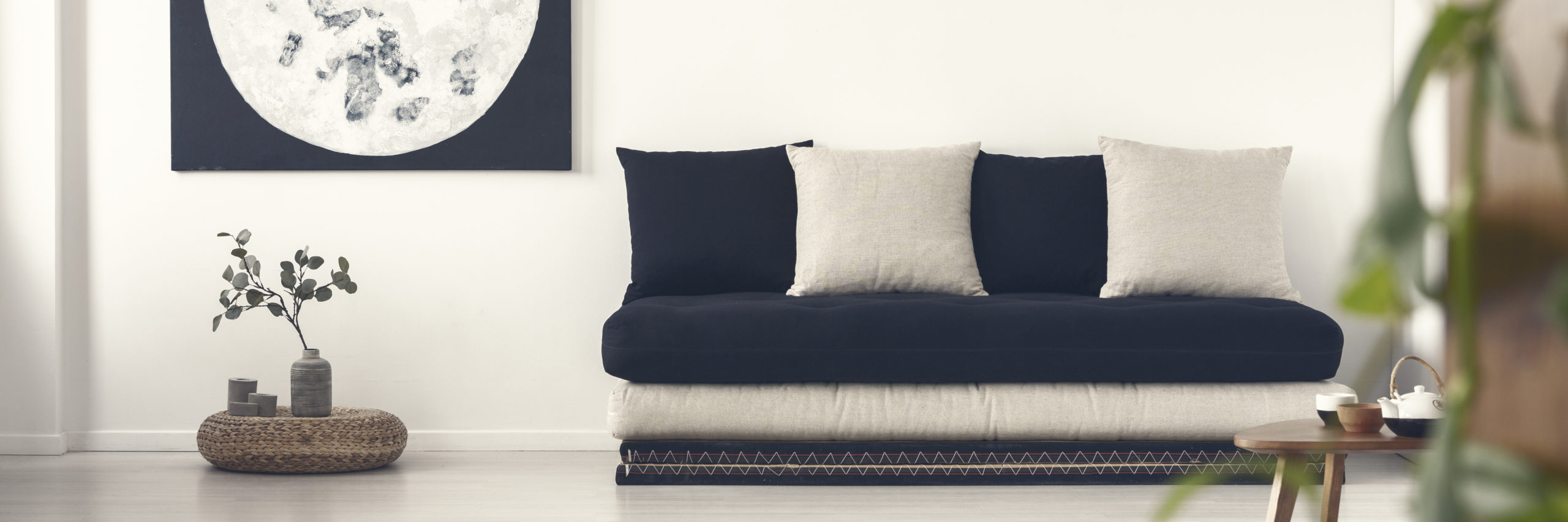 Plant on pouf next to black sofa with pillows in white living room interior with moon poster. Real photo